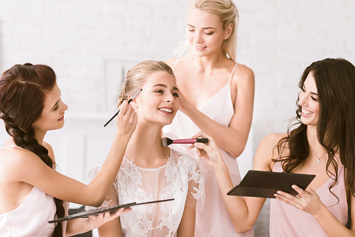Cheerful bridesmaids helping the bride to get ready